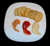 Pommes chips avec de la sauce d'isolement sur le noir Images stock
