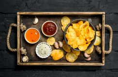 Pommes chips avec des sauces dans un plateau en bois image stock