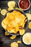 Pommes chips avec des sauces et le romarin différents images libres de droits