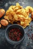 Pommes chips crémeuses cuites de grain de poivre, chips de casse-croûte avec du sel de mer sur le conseil en pierre avec le pilon Image libre de droits