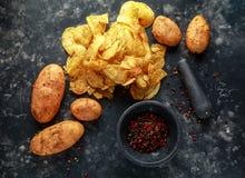 Pommes chips crémeuses cuites de grain de poivre, chips de casse-croûte avec du sel de mer sur le conseil en pierre avec le pilon Photos stock