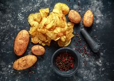 Pommes chips crémeuses cuites de grain de poivre, chips de casse-croûte avec du sel de mer sur le conseil en pierre avec le pilon Image stock