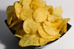 Pommes chips croustillantes, dans un plat, sur un fond blanc Plan rapproché Photographie stock libre de droits