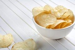 Pommes chips d'or délicieuses dans une cuvette blanche sur un fond en bois blanc photographie stock