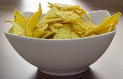 Pommes chips dans la cuvette blanche sur la table en bois Images stock