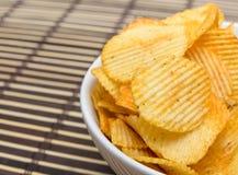 Pommes chips dans la cuvette blanche sur le tapis en bambou Image stock