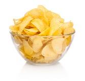 Pommes chips dans le bol en verre d'isolement sur le fond blanc Photos libres de droits