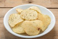 Pommes chips dans un plat blanc sur le fond en bois Images libres de droits