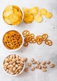 Pommes chips de bretzel et et pistache dans la cuvette en céramique blanche sur le fond en pierre de table de cuisine Casse-croût photos libres de droits