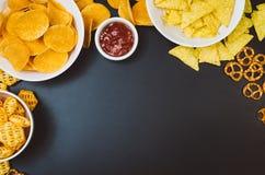 Pommes chips et casse-croûte sur la table noire d'ardoise, vue supérieure photographie stock