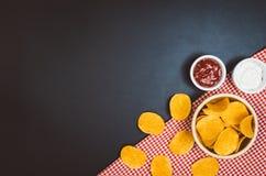 Pommes chips et casse-croûte sur la table noire d'ardoise, vue supérieure photographie stock libre de droits