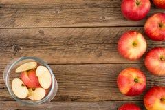 Pommes coupées en tranches dans un bol en verre sur la vieille table en bois Image libre de droits