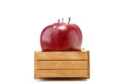 Pommes dans la boîte en bois d'isolement sur le blanc Images stock