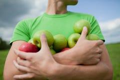 Pommes dans les mains d'un type intense photographie stock