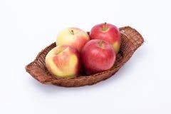 Pommes dans un panier d'isolement Photos stock
