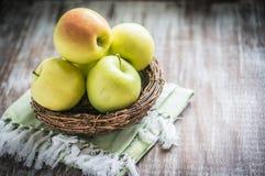 Pommes dans un panier sur le fond rustique images stock
