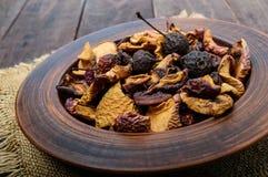 Pommes de fruits secs, poires, abricots, baies dans une cuvette sur le fond en bois foncé Images stock