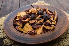 Pommes de fruits secs, poires, abricots, baies dans une cuvette sur le fond en bois foncé Photographie stock libre de droits