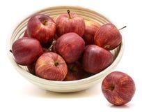 Pommes de gala dans la cuvette de rotin d'isolement sur le fond blanc photographie stock