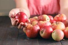 Pommes de prise de femme sur le fond en bois Photos stock