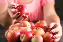 Pommes de prise de femme sur le fond en bois Photo stock