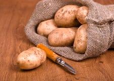 Pommes de terre avec le couteau pour nettoyer des légumes Photos stock