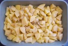 Pommes de terre coupées en tranches à l'oignon italien et au romarin prêts à être fait cuire au four Photos stock