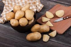 Pommes de terre coupées en tranches par jeunes sur la fin en bois de table  Image libre de droits