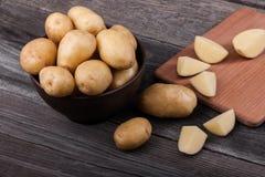 Pommes de terre coupées en tranches par jeunes sur la fin en bois de table  Photo stock