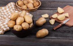 Pommes de terre coupées en tranches par jeunes sur la fin en bois de table  Photos libres de droits