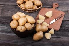 Pommes de terre coupées en tranches par jeunes sur la fin en bois de table  Images libres de droits