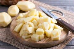 Pommes de terre crues, cubes coupés sur un conseil en bois Images stock