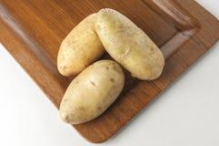 Pommes de terre crues sur le plateau en bois Images stock