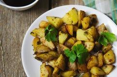 Pommes de terre cuites au four avec de la sauce d'un plat blanc Photo stock