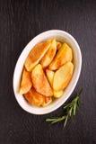 Pommes de terre cuites au four avec des épices dans la cuvette blanche Photos stock