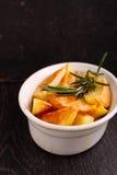 Pommes de terre cuites au four avec des épices dans la cuvette blanche Image stock