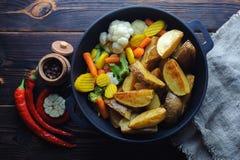 Pommes de terre cuites au four avec des légumes dans un poivre de poêle et de piment images stock