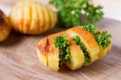 Pommes de terre cuites au four avec les herbes fraîches, rayées sur un support en bois photo stock