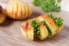 Pommes de terre cuites au four avec les herbes fraîches, rayées sur un support en bois image libre de droits