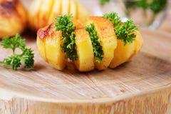 Pommes de terre cuites au four avec les herbes fraîches, rayées sur un support en bois image stock