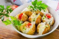 Pommes de terre cuites au four chaudes avec les légumes et la crème sure photos stock