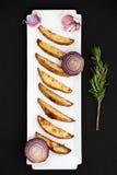 Pommes de terre cuites au four et lus rouges avec le romarin et l'ail sur un r blanc Photos libres de droits