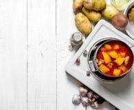Pommes de terre cuites avec de la viande et des épices dans un cuiseur électrique sur la table en bois blanche L'espace libre pou Photos stock