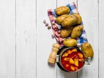 Pommes de terre cuites avec de la viande et des épices sur le fond en bois blanc L'espace libre pour le texte Images stock