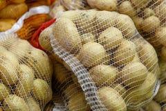 Pommes de terre dans des sacs de maille d'un marché Image libre de droits