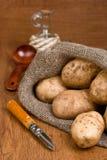 Pommes de terre dans le sac à toile de jute avec un couteau rustique Photos stock