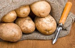 Pommes de terre dans le sac à toile de jute avec un couteau rustique Photographie stock libre de droits