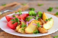 Pommes de terre et légumes rôtis Cales rôties de pomme de terre, brocoli bouilli, tranches fraîches de tomate, oignon rouge, pers Images libres de droits