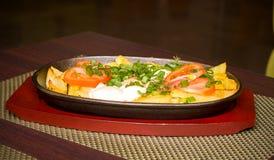 Pommes de terre et oeufs au plat avec des tomates et des verts Photographie stock