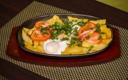 Pommes de terre et oeufs au plat avec des tomates et des verts Photo libre de droits